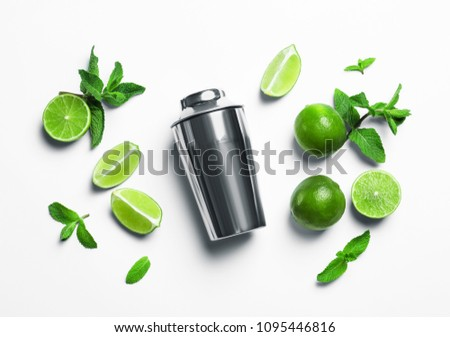 Flat lay composition with lime, mint and shaker on light background. Refreshing beverage ingredients #1095446816