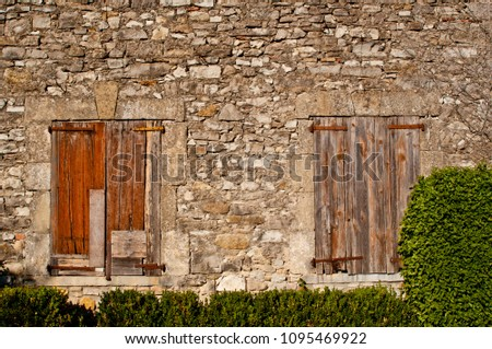 old boarded up windows in stone wall #1095469922