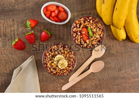 Acai berry cups on wooden background #1095511565