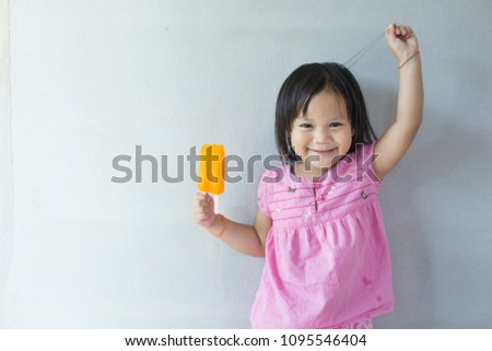 Little girl wearing a pink shirt eating a orange  ice cream on a wall. #1095546404