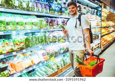 young smiling man choosing products in grocery store. shopping concept. lifestyle #1095591962