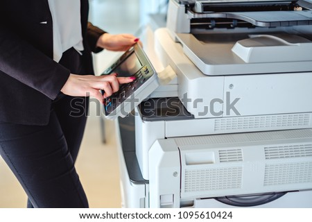 Woman standing and pressing button on a copy machine in the office Royalty-Free Stock Photo #1095610424