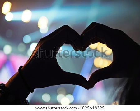 K-Pop music theme or Live concert background with silhouette hands of audience making heart shaped hand gesture for artist supporting on blurred background of a large stage with bokeh light.