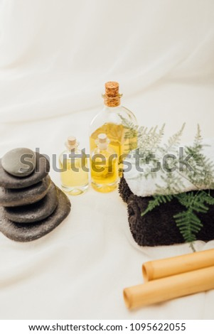 close up view of arrangement of spa treatment accessories with towels, pebbles and essential oil on white background #1095622055