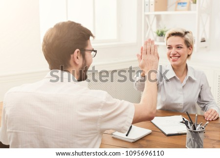 Winner business partners happy, successful, in white modern office, sitting at workplace. Colleagues giving high five, success concept #1095696110