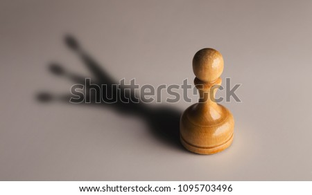 Trust yourself, self confidence concept. Wooden chess pawn with king shadow on gray background, motivation poster Royalty-Free Stock Photo #1095703496