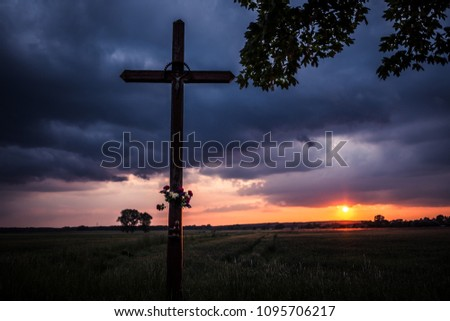 wayside crucifix and sunset iN the background