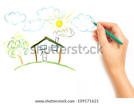 Wman's hand with the pencil drawing the dream home on a white sheet of paper