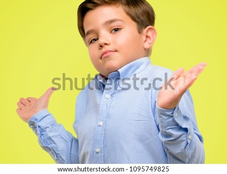 Handsome toddler child with green eyes doubt expression, confuse and wonder concept, uncertain future over yellow background #1095749825