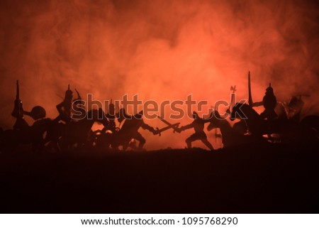 Medieval battle scene with cavalry and infantry. Silhouettes of figures as separate objects, fight between warriors on dark toned foggy background. Night scene. Selective focus #1095768290