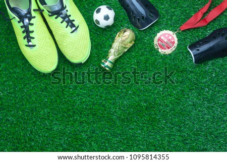 Table top view aerial image soccer or football tournament season background.Flat lay prepare objects for competitive match the shoe with gold medal & ball on the artificial green grass wallpaper. #1095814355
