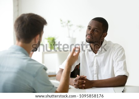 African American employer listening attentively to caucasian job applicant talking at work interview, being friendly and interested to candidate. Concept of recruiting, employment, hiring Royalty-Free Stock Photo #1095858176