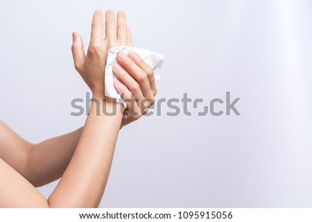 Woman cleaning her hands with white soft tissue paper. isolated on a white backgrounds #1095915056