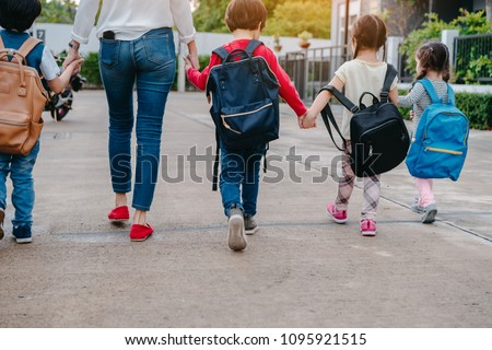 Mother and pupil and kids holding hands going to school in first class with schoolbag or satchel walking to school bus, Parent and son,sister preschool  Royalty-Free Stock Photo #1095921515