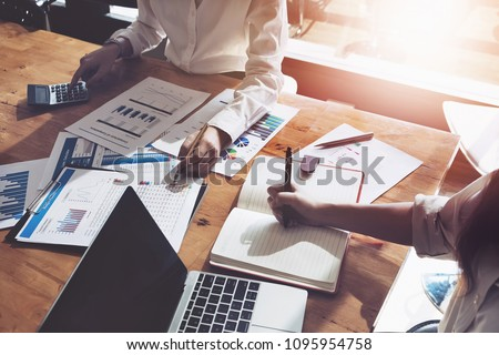 business consulting or finance budget plan, business advisor holding pen pointing to explain method profit with business owner use pen write to notebook and use laptop computer. #1095954758