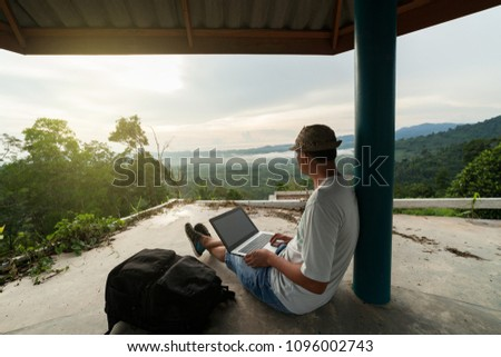Young man sitting using laptop against scenery landscape forest in sunset or sunrise time,Travel man work job and relaxing outdoors in phang nga Thailand #1096002743