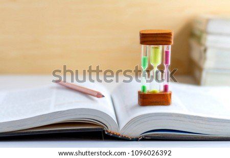 Sand dropping through the bulb of the hourglass and textbook placed on the table. with copy space for your text. #1096026392