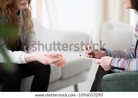 Cropped photo of a therapist writing down notes during therapy with her female patient Royalty-Free Stock Photo #1096053290