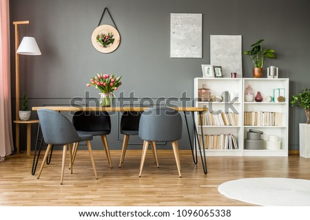 White wooden rack with books, decor and fresh plants standing in grey dining room interior with flowers on hairpin table #1096065338
