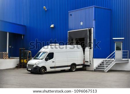van in loading and unloading commercial cargo in warehouse dock #1096067513