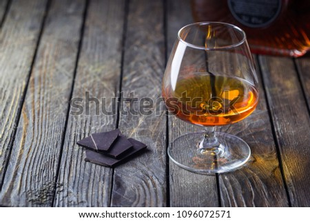 Glasse of brandy or cognac and chocolate on dark background. #1096072571