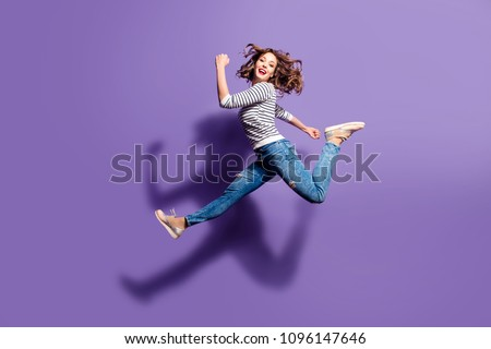 Portrait of sportive active girl in motion jumping over in the air isolated on violet background having perfect stretching looking at camera Royalty-Free Stock Photo #1096147646