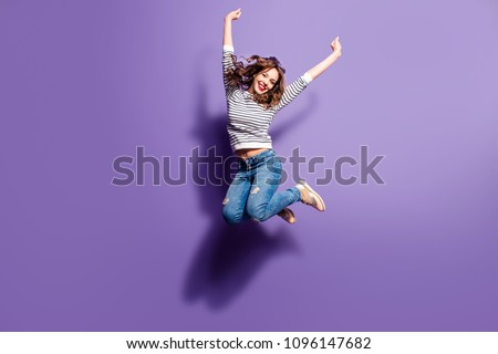 Portrait of cheerful positive girl jumping in the air with raised fists looking at camera isolated on violet background. Life people energy concept #1096147682
