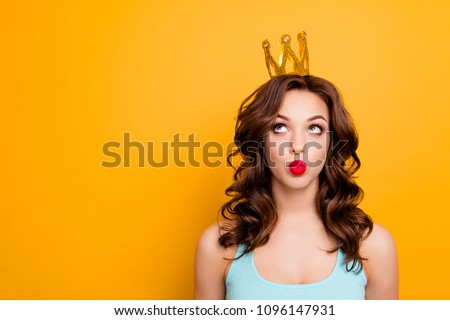 Portrait with copyspace empty place of funny stupid girl looking at crown on head with eyes sending kiss with pout lips isolated on yellow background advertisement concept
