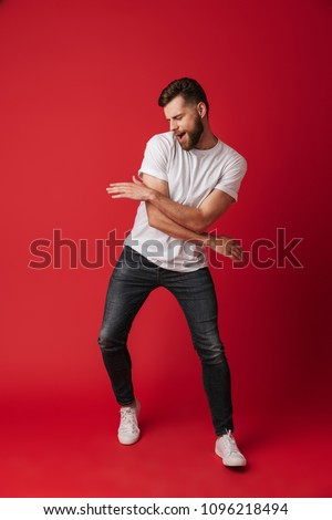 Photo of handsome young man dancing isolated over red wall background. Royalty-Free Stock Photo #1096218494