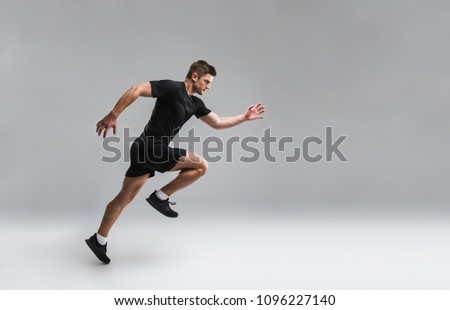 Full length portrait of a focused young sportsman running fast isolated over gray background Royalty-Free Stock Photo #1096227140