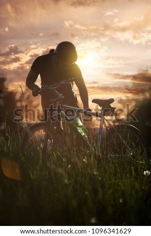 Young man in sunset sitting on his bike in nature #1096341629