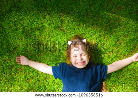 Little girl is lying on the green grass. Happy child. Copy space.  #1096358516