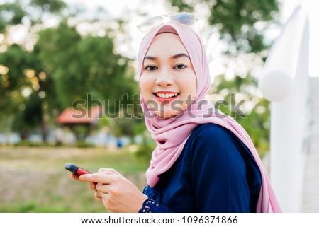 pretty hijab women use a cellphone #1096371866