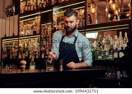 Stylish brutal barman in a shirt and apron makes a cocktail at bar counter background. #1096432751