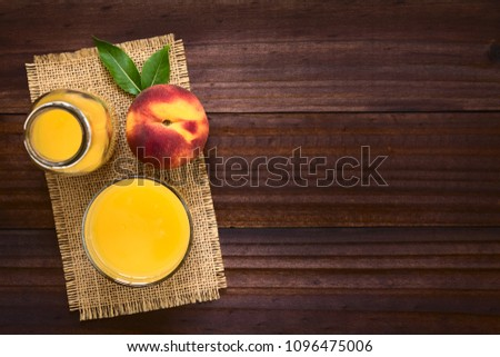Peach juice or nectar with fresh ripe peach fruit on the side, photographed overhead on dark wood with natural light (Selective Focus, Focus on the top of the juice and the top of the whole fruit) #1096475006
