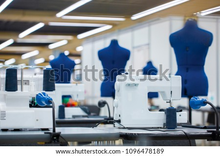 Interior of garment factory . Closes making atelier with several sewing machines. Tailoring industry, fashion designer workshop, industry concept Royalty-Free Stock Photo #1096478189