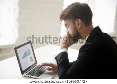 Serious thoughtful businessman looking at laptop screen, thinking about rates and sales growth, company successful strategy, analyzing financial statistics, solving business problem #1096537727