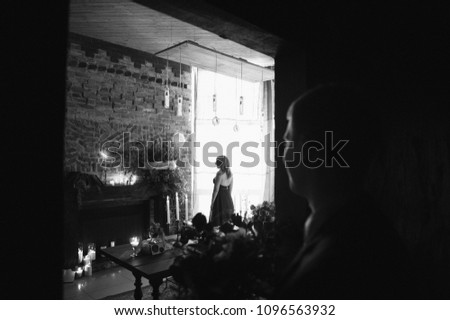Black and white photo The bride gathers in the morning near the window. The room is loft style. Green wedding dress. #1096563932