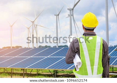 Young business man engineer with yellow helmet at solar panel and wind generators power plant construction site background #1096652174