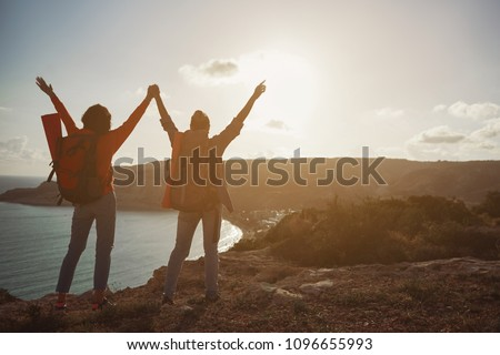 Back of tourists standing with raised arms. They enjoying seascape in front of them. Copy space in right side #1096655993