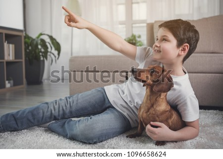 Look there. Dreamful kid is pointing finger up and smiling. His dog is looking there with interest #1096658624