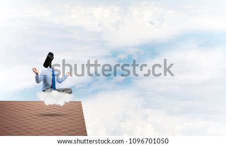 Faceless businessman with camera zoom instead of head sitting in lotus pose #1096701050