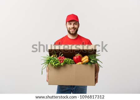 Delivery Concept: Handsome Caucasian grocery delivery courier man in red uniform with grocery box with fresh fruit and vegetable #1096817312