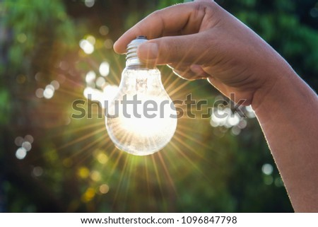 hand holdging light bulb with solar energy. power eco concept #1096847798