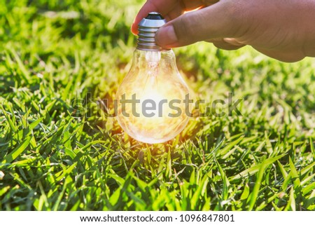 hand holdging light bulb on grass with solar energy. power eco concept #1096847801