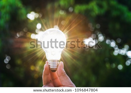 hand holdging light bulb with solar energy. power eco concept #1096847804
