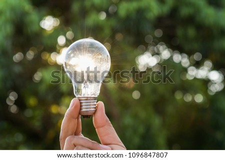 hand holdging light bulb with solar energy. power eco concept #1096847807