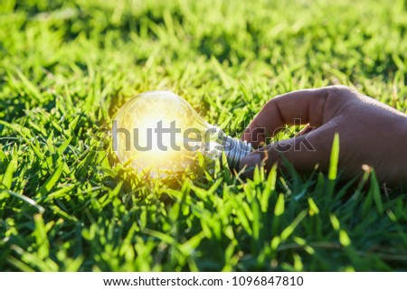 hand holdging light bulb on grass with solar energy. power eco concept #1096847810