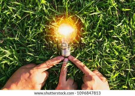 hand holdging light bulb on grass with solar energy. power eco concept #1096847813