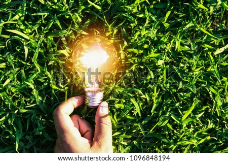 hand holdging light bulb on grass with solar energy. power eco concept #1096848194